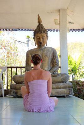 Monja vor dem Buddha