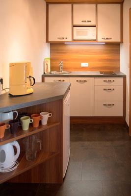 Küche mit Spülmaschine, Herd (2 Platten), Kühlschrank mit Gefrierfach, Kaffeemaschine, Mikrowelle