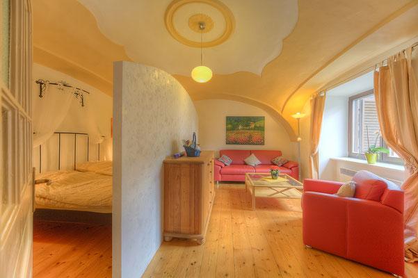 Wohnzimmer mit Schlafbereich - Rechts 3er-Couch und Sessel, links  getrennt durch eine freistehende Wand  das Schlafabteil mit zwei Kleiderschränken