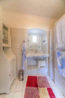 Bad - Blick auf den Waschtisch, links der Schrank, rechts hinter der Fliesenwand ist die Dusche