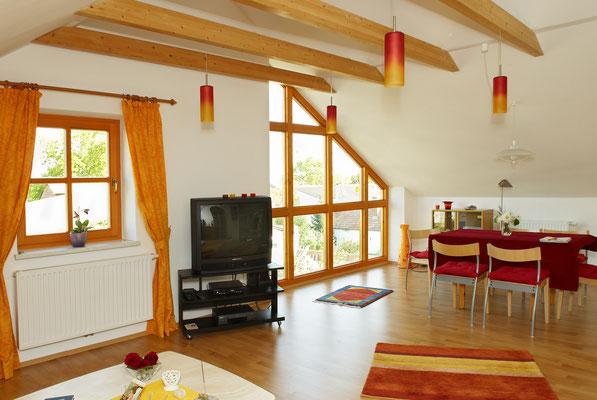 Wohnzimmer mit Flat-TV mit Blick aus dem Panoramafenster Im Bild auch der Esstisch