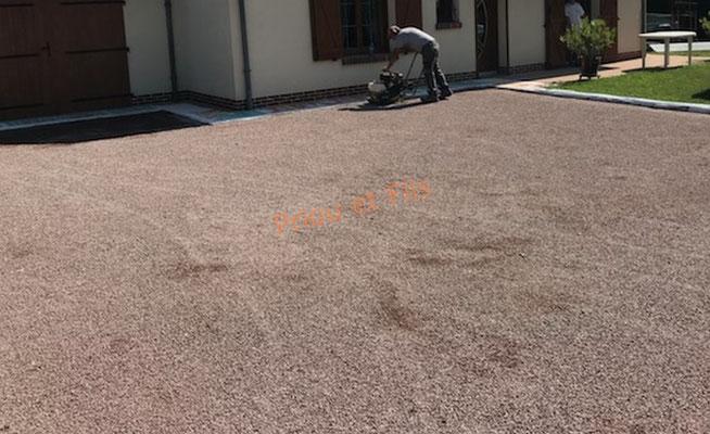 Application de l'émulsion avec du gravillon rose puis compactage de la surface