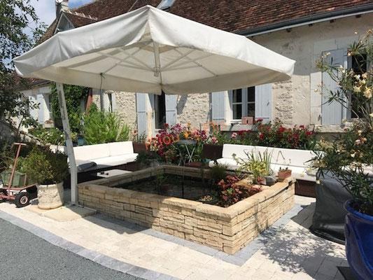 terrasse en pavés en pierre naturelle aménagée par le client et petit bassin terminé