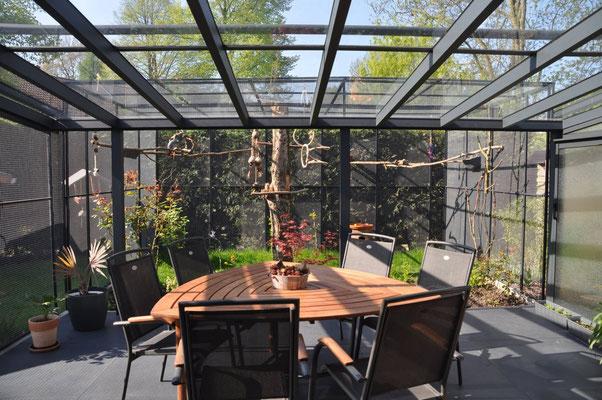 Volierenanbau an einer überdachten Terrasse. So können die Vögel direkt vom Wohnbereich auch in die Außenanlage gelangen. Das Aluminium ist farblich auf die Terrassenüberdachung abgestimmt.