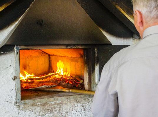 Bernd Storch am selbst gebauten Holzbackofen beim Pizzabacken