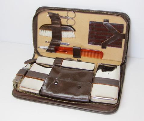 Reis-set voor persoonlijke verzorging  met een glazen flesje in een lederen etui.