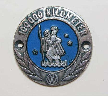 Een verzilverd embleem met Sint-Christoffel voor 100.000 gereden kilometers van Volkswagen.