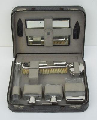 Een reis-set bestaande uit een met leder bekleed koffertje met glazen flesjes en vernikkelde deksels, doppen e.d.