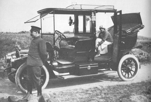 De chauffeur is erg discreet terwijl mevrouw met haar kousen bezig is, van de fotograaf kun je dat niet zeggen. De auto is een Delahaye uit 1913.
