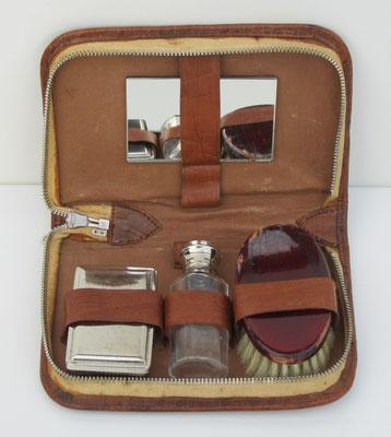 Een reis-set voor persoonlijke verzorging met een glazen flesje in een lederen etui.