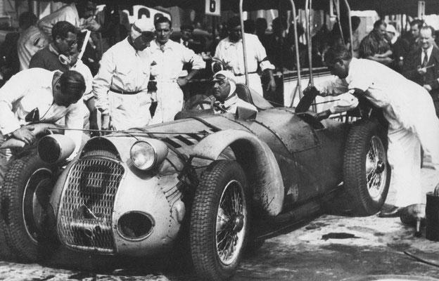 """René Dreyfus naast de Delahaye Type 145 4,5 liter twaalfcilinder grand prix racewagen, omgebouwd tot """"sportwagen"""" door toevoeging van verlichting en spatborden."""