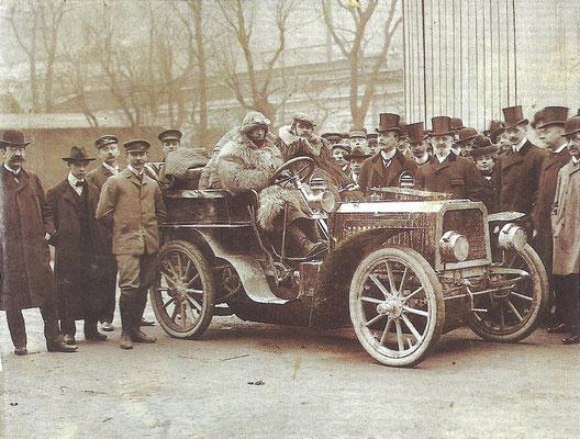 Engineer Ettore Bugatti achter het stuur van de De Dietrich-Bugatti, Eugene de Dietrich staat achter de motorkap en kijkt richting camera.