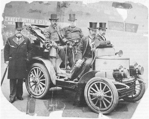 Leon Serpollet zit aan het stuur van zijn stoomwagen op de auto-tentoonstelling van Cardingley in 1901.