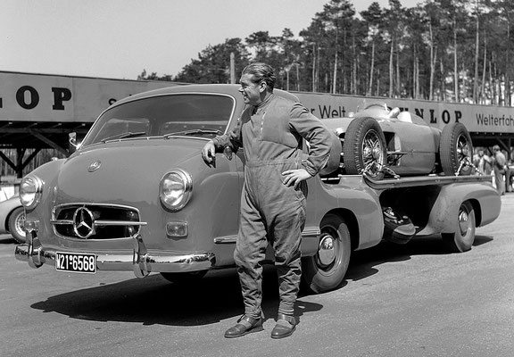 "Rudolf Uhlenhaut in 1955 bij de Mercedes-Benz high-speed racing car transporter ""Das blaue Wunder"" met daarop een Mercedes-Benz W 196 R Monoposto Formule 1 racewagen."