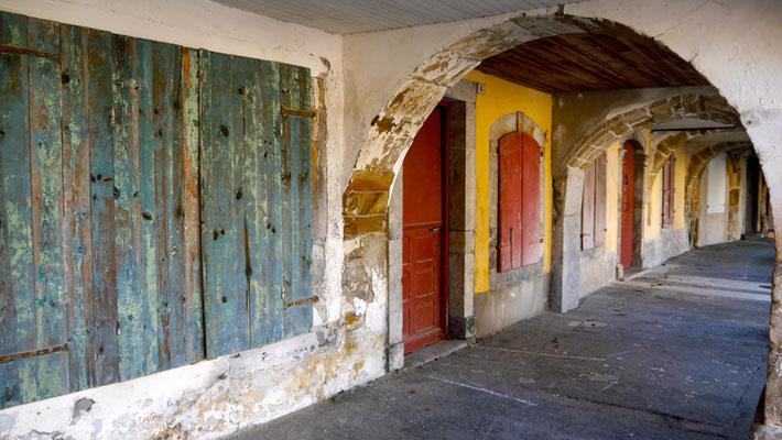 Sous les arcades, les portes cloutées.