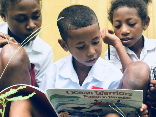 Ein Kind aus Kabui liest die Geschichte seinen Freunden vor