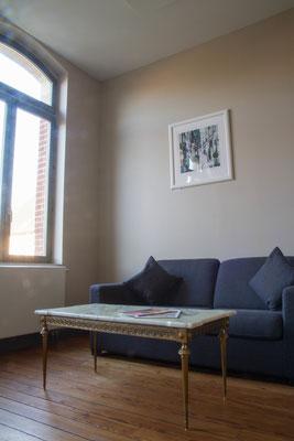 Salon avec télévision, table basse et canapé