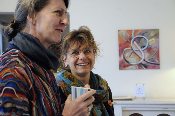 Claudia Groß (rechts) im Gespräch; im Hintergrund ein Bild von ihr