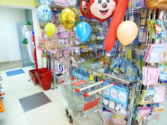 Вход в  в торговый зал компании Волшебник, рядом расположены покупательские корзины и телеги для оптовых покупателей.