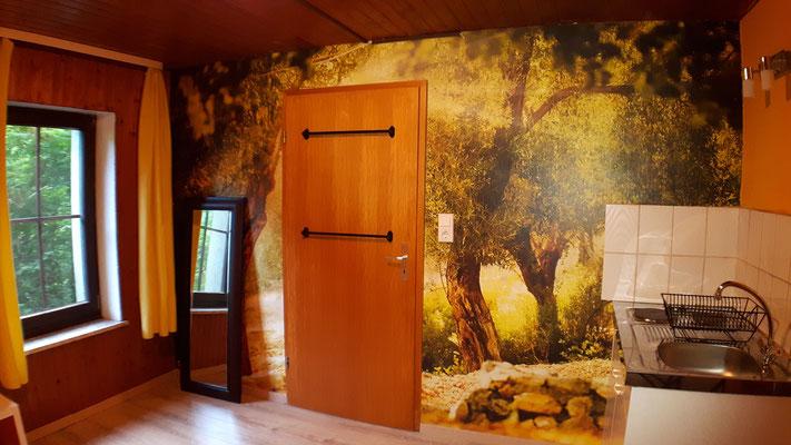 Eingangstür mit Olivenbaumansicht und Küchenzeile