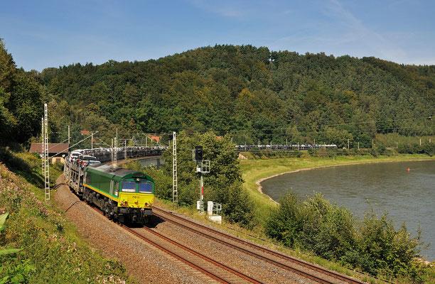 Eine Class 66 der Ascendos Rail Leasing legt sich am Elbhäuserweg bei Königstein mit ihrem Autozug in die Fotokurve, September 2011.