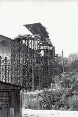 Die vorgefertigten Stahlelemente der Fahrbahn für die Behelfsbrücke werden per Eisenbahnkran eingehoben. 1984, Foto: Archiv Sven Kasperzek.