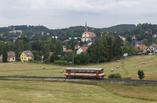 """810 165-1 ( jetzt mit der Aufschrift """"Regio Mouse"""") auf seinem Weg nach Rumburk in der Ortslage von Mikulášovice. Im Hintergrund das Kostel sv. Mikuláše, 29.07.18"""