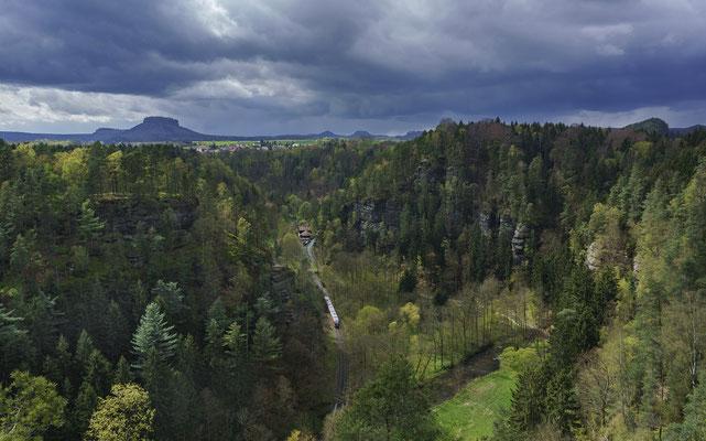 Blick von den Ochelwänden bei Porschdorf hinunter ins Sebnitztal. Auch ein kleines Stückchen Einsicht auf die Strecke bietet sich hier. Dort ist ein Desiro der Nationalparkbahn unterwegs nach Rumburk. April 2017.