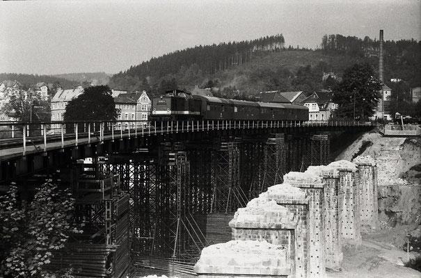P 18873 nach Bad Schandau hat Sebnitz gerade verlassen . Vom ehemaligen schönen Sebnitzer Viadukt sind nur noch die Pfeiler zu sehen. Der Zugverkehr lief während dem Neubau über eine Behelfsbrücke. Sommer 1986, Foto & Infos: Lutz Morgenstern