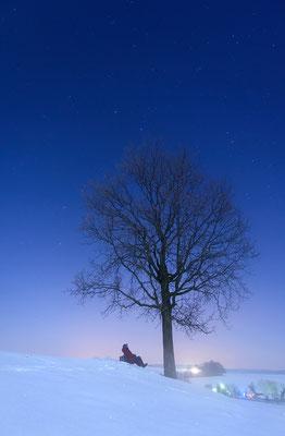 Nach ungefähr 45 Minuten begann die Technik zu gefrieren, auf den Linsen bildete sich ein Eisrand. Zum Schluss fotografierte ich noch meinen Vater, der hier unter einem Bäumchen die Aussicht in den Sternenhimmel genießt. ISO 1600, 24mm, f/2.8, 10 Sek.