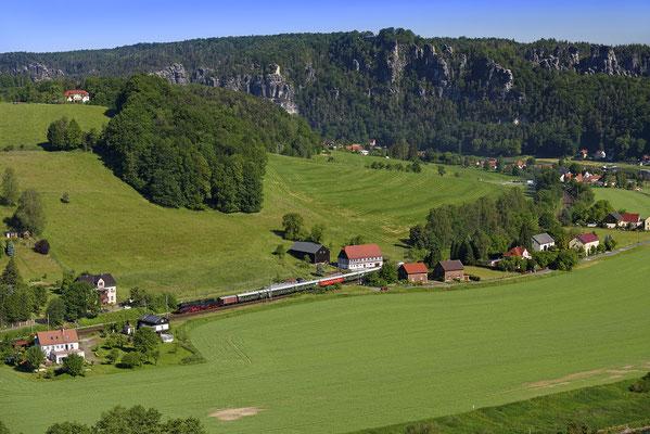 Blick vom Hörnelweg hinab ins Elbtal. Im Hintergrund das Basteimassiv und Rathen. Auf der Elbtalbahn ist ein Dampfzug unterwegs nach Tschechien. ISO 200, 70mm, f/6.3, 1/400sek.