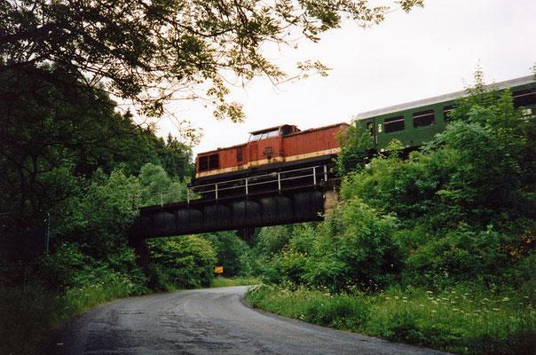 Ein Zug mit der 112 063-3 überquert von Sebnitz kommend kurz nach dem Haltepunkt Amtshainersdorf die Straße (nach Ulbersdorf) und den Sebnitzbach, um gleich darauf in den Tunnel 2 zu verschwinden, 1991. Text & Foto: Archiv Axel Förster.