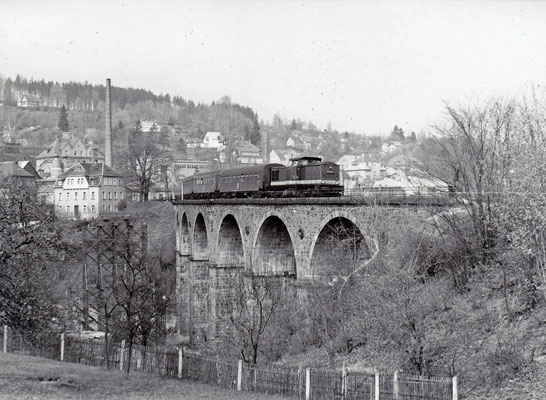 Eine typische Reichsbahngarnitur der 80ér Jahre mit V100 und Reko 4-Achsern unterwegs von Bautzen nach Bad Schandau auf dem Sebnitzer Stadtviadukt. Auch hier zu erkennen: Erste Stützelemente der Behelfsbrücke. 1984, Foto: Archiv Sven Kasperzek.