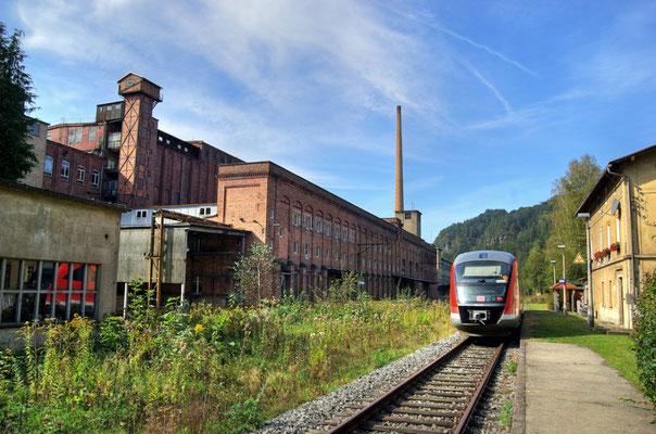 Die Regionalbahn Neustadt-Bad Schandau hat Goßdorf-Kohlmühle erreicht, Überragt wird die Szenerie vom ehemaligen VEB Linoleumwerke Kohlmühle ( heute Likolit ), 27.09.09