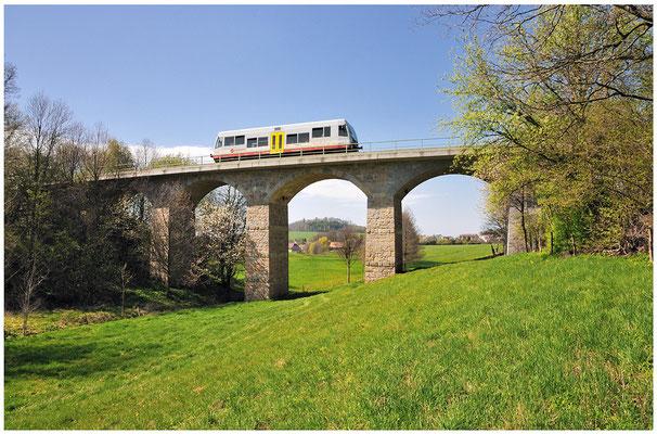Auf der Rückfahrt nach Neustadt habe ich den kleinen Triebwagen auf dem fotogenen Viadukt bei Langenwolmsdorf abgelichtet. Durch den mittleren Brückenbogen geht der Blick bis zur Burg Stolpen. 27.04.2012