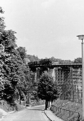 Eine BR 86 mit Sonderzug nach Bad Schandau auf der Behelfsbrücke in Sebnitz, deutlich zu erkennen die schon fertigen neuen Betonpfeiler des rekonstruierten Viaduktes.