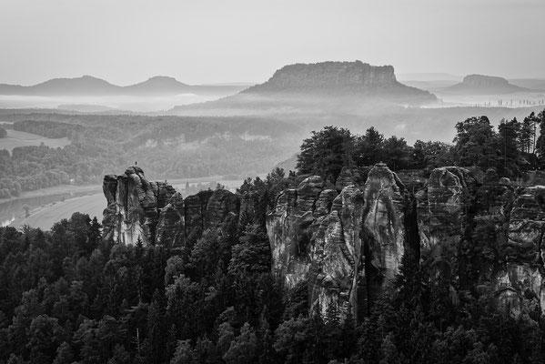 Blick von der Wehlnadel hinüber zur Bastei. Dahinter dominant der Lilienstein, rechts davon der Pfaffenstein. Die eher eintönige Stimmung bewegte mich zur Umwandlung in Schwarz-Weiß. ISO 50, 70mm, f/11.0, 1 Sek.