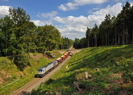 """ITL """"Blue Tiger"""" 250 006 mit schwerer Last aus dem Steinbruch Oberottendorf. Nachdem die Fuhre den Bahnhof Neukirch / Lausitz (West) verlassen hat geht es weiter durch einen Waldeinschnitt in Richtung Bischofswerda und von dort nach Dresden, August 2011."""