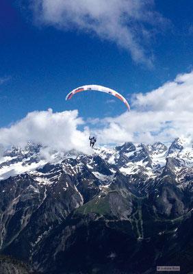 Photo d'un parapente devant une chaîne de montagne