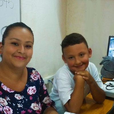 Empresaria con hijo en la clase de tecnologías, aprendiendo a utilizar herramientas en Google para aprovecharlas en su proyecto.