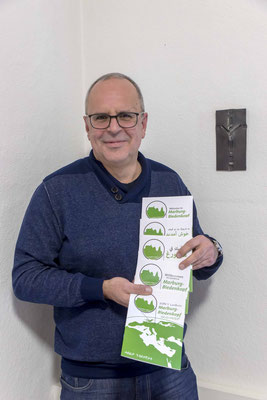 Diakoniepfarrer Ulrich Kling-Böhm mit der verschiedenen Ausgaben der Willkommensbroschüre (Foto: Karl-Günter Balzer)