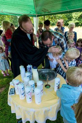 Pfarrer Matthias Weidenhagen tauft ein Baby