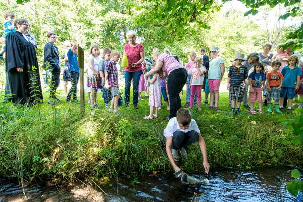 Die Kinder holen das Taufwasser