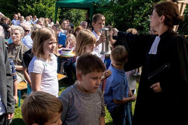 Pfarrerin Anja Fülling sendet die Kinder aus, das Taufwasser zu holen