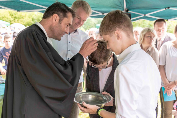 Pfarrer Dierk Brüning tauft einen Jugendlichen