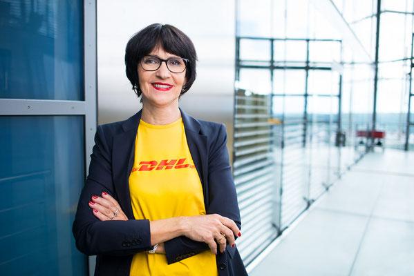 Eine DHL Mitarbeiterin posiert für ein Portrait. Corporate-Fotografie, Businessportrait Portrait