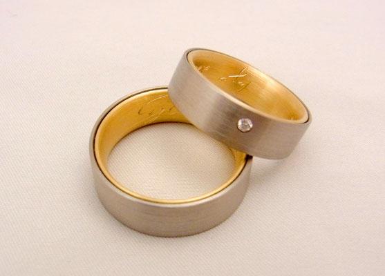 Handgravierte, zweifarbige Trauringe in Gelb- und Weißgold. Im Damenring ist als kleiner Akzent ein weißer Brillanten eingerieben.