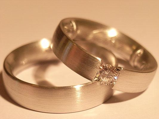 Weißgoldspannring mit weißem Brillanten als Damenring, der Herrenring klassisch schlicht.