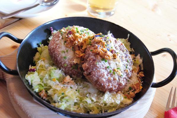 Kaspressknödel auf warmem Krautsalat.