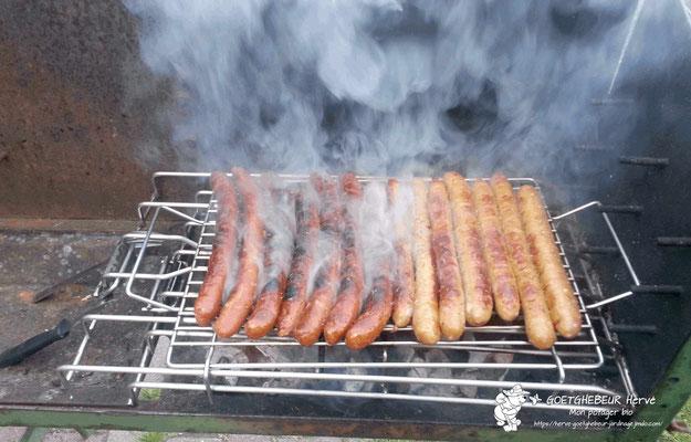 Assortiment de merguez et de saucisses en pleine cuisson sur le barbecue.